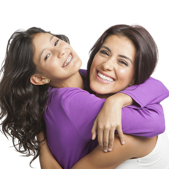 Mother hugging her young daughter after pediatric orthodontics appointment
