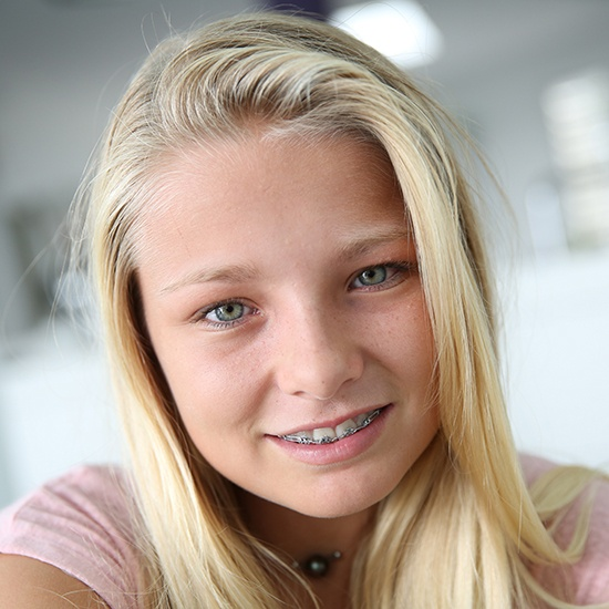 Smiling teen girl with traditional metal braces