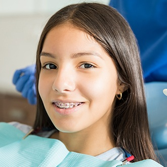 Smiling teen girl with braces in orthodontic treatment chair