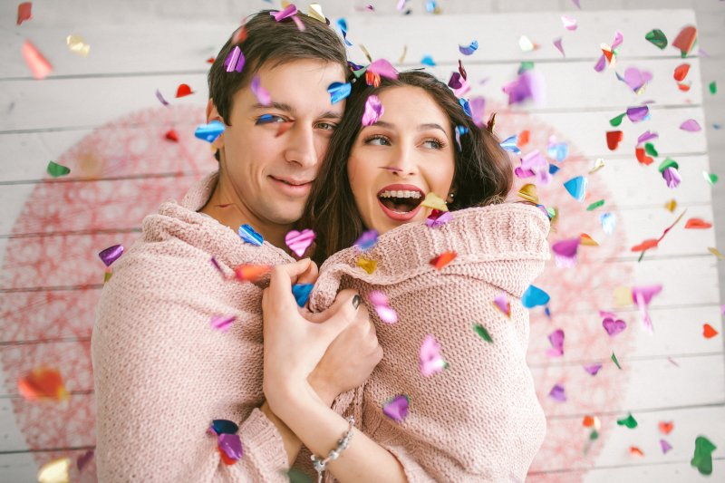 Couple with braces smiling and dancing in confetti