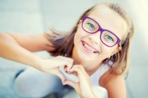 Young girl with braces making heart with her hands
