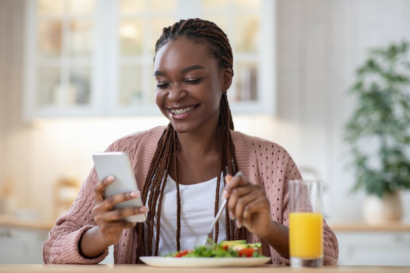 Woman with braces smiling while eating vitamin-rich lunch